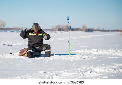 Fisherman on the river in winter day to catch fish. Ice fishing , fishing from under the ice , winter fishing tackle. Ice axe, winter fishing rod, a jig, a spinner, a rocker.