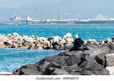 Fisherman on rocks in the Bay of Naples