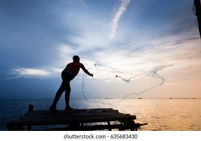 Fisherman on scaffolding casting a net for catching fish in the sea in the sunset,  silhouette and blurry photo.
