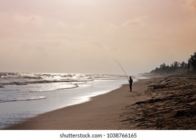 A fisherman on the shore of the ocean in direct sunlight. To fish the bait. A real man's hobby, food mining. Silhouette