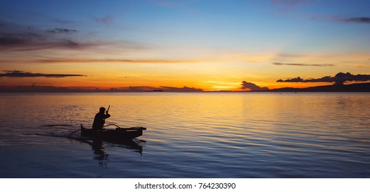 Fisherman on small boat on the sea at sunset. Banner