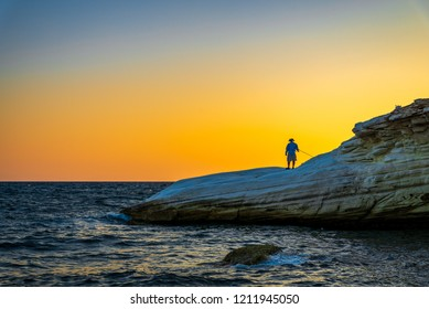 Fisherman on white stones in sunset in Cyprus