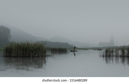 Fisherman on wood boat hunting with long stick on a foggy morning with church in background, Van Long Wetland Nature Reserve, Ninh Binh, Vietnam, Asia