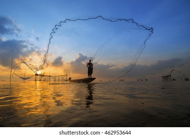 Fisherman on wooden boat casting a net for catching fish