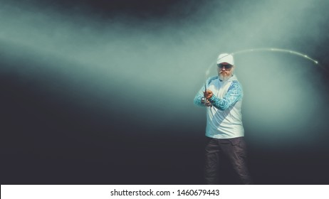 Fisherman performs casting spinning. Isolated image on a dark background with a haze.