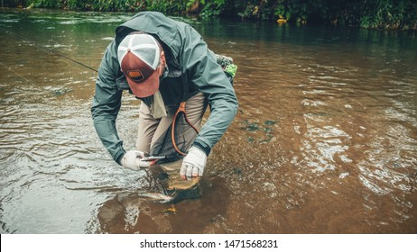 A fisherman photographs a caught fish on a smartphone.