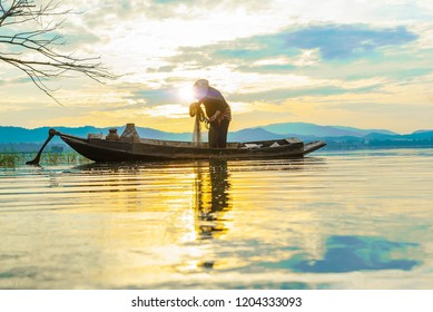 Fisherman prepare fishnet in old boat on lake  early morning with sunshine on back side.