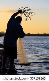 Fisherman prepares net at sunrise