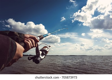 the fisherman pulls the fish out of the water on the lake. Closeup of a boys hand holding a fishing rod and reel