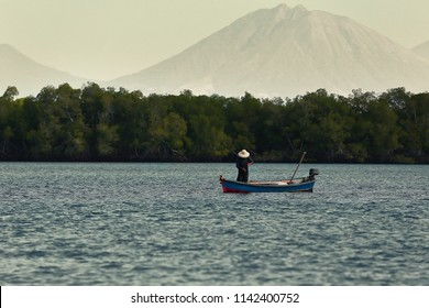 A fisherman pulls his net out of the water while on his small traditional boat at El Salvador, Central America