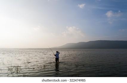 fisherman in reservoir lamtakong, nakhon ratchasima province, thailand