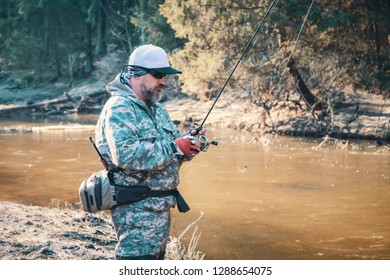 Fisherman with rod on the river bank.