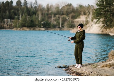 Fisherman with rod, spinning reel on the river bank. Fishing for pike, perch, carp. Woman catching fish, pulling rod while fishing at the weekend. Girl fishing from beach lake or pond with text space.