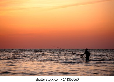 Fisherman in the sean on vivid orange sunset. Sochi, Russia