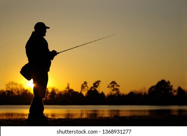 A fisherman silhouette fishing at sunset. Freshwater fishing, catch of fish