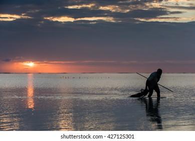 Fisherman silhouette at sunrise