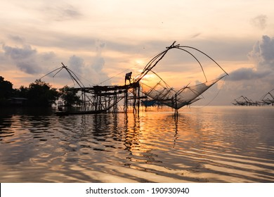 Fisherman silhouette at sunrise in Asia