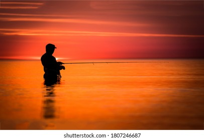 Fisherman silhouette a sunrise lake. Sunrise fisherman slhouette. Fisherman at fishing at sunrise