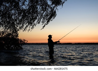 Fisherman silhouette at sunset on the lake while fishing