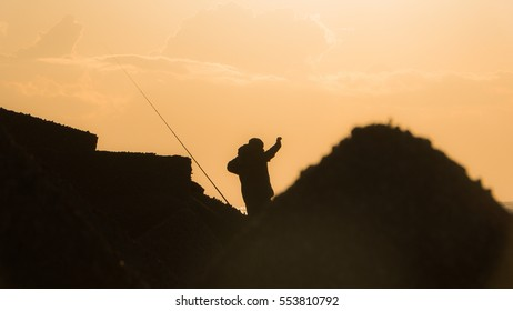 Fisherman silhouette while fishing at the pier in Sicily