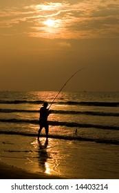 Fisherman Silhouetted in a Beach Sunrise
