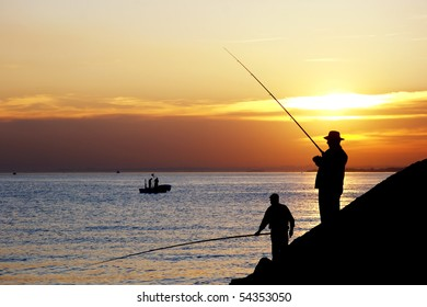 Fisherman silhouettes against sunset