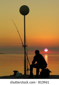 fisherman sitting by the sunset