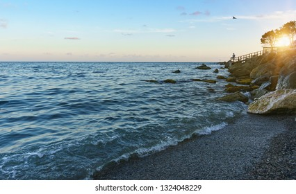 Fisherman sitting on a rocky shore and fishing in the sea. A beautiful sunset in the Crimea. Yalta