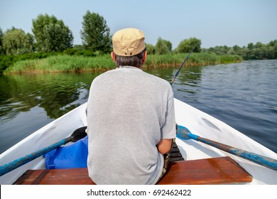 Fisherman sitting on a rowing boat and fishing in the middle of the pond.View from the back