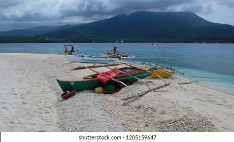 The fisherman is sleeping, hiding from the wind. Uninhabited white island near Camiguin, Philippines.