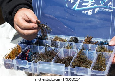 A fisherman sorts through his tackle box containing homemade and store bought bass jigs, complete with lead heads and glitter skirts.