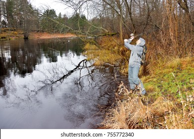 fisherman with a spinning catches a pike on the river bank during the autumn season