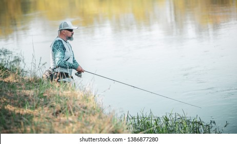 Fisherman with spinning on the river bank.