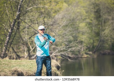 Fisherman with a spinning rod catching fish on a river