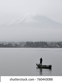 Fisherman standing fishing alone on small motor boat at lake Kawaguchi in the morning with mount Fuji in background. Portrait view. Low vibrance tone. Reminding of old time. Feeling of peace and quiet