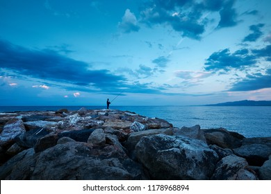 Fisherman standing on the pier in the morning before sunrise, by the sea, with it's rod up, fishing