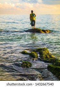 Fisherman standing on a stone waiting throws fishes