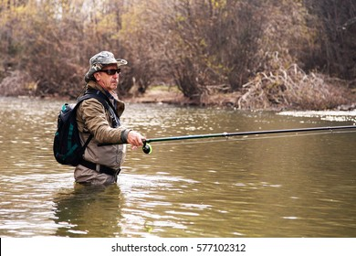 Fisherman standing in the river when fishing for grayling in autumn