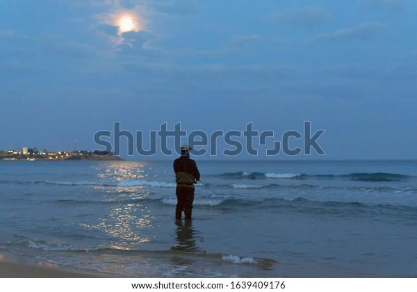 fisherman-standing-seashore-hooks-fish-6