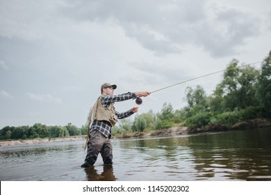 Fisherman is standing in shallow and fishing. He is throwing forward spoon for it. Guy holds fly rod in hands. He is using it. Man wears waders, vest and cap to protect the body.