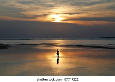 fisherman standing in shallow water during sunset