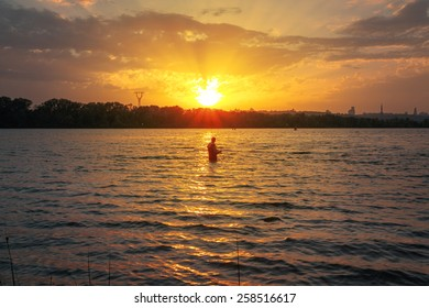 fisherman standing  waist-deep in the river water, against bright sunset. Kiev, Ukraine.