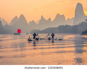 Fisherman stands on traditional bamboo boats at sunrise (boat with a red sail in the background) - The Li River, Xingping, China.