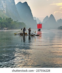 Fisherman stands on traditional bamboo boats at sunrise (boat with a red sail in the background) - The Li River, Xingping, China