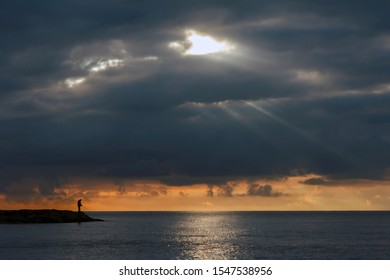 fisherman at sunrise with crepuscular rays