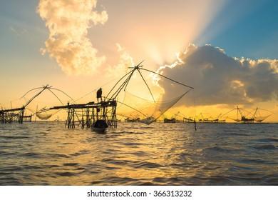 Fisherman with sunrise at Pakpra, Phatthalung ,Thailand