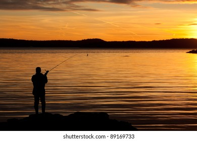 A fisherman in sunset at the coast.
