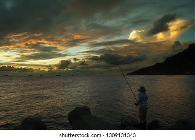 Fisherman at sunset in Xi Zi Wan bay, Kaohsiung, Taiwan