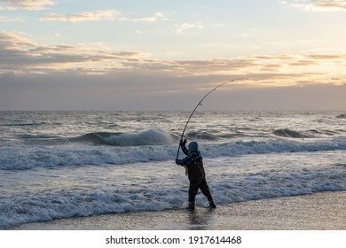 A fisherman swinging his pole into the sea