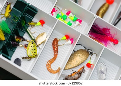 A fisherman tackle box with lures and gear for fishing.